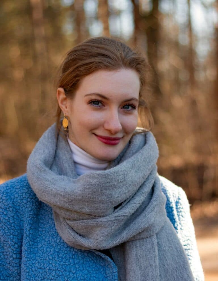 Carina's headshot in a blue scarf and jacket